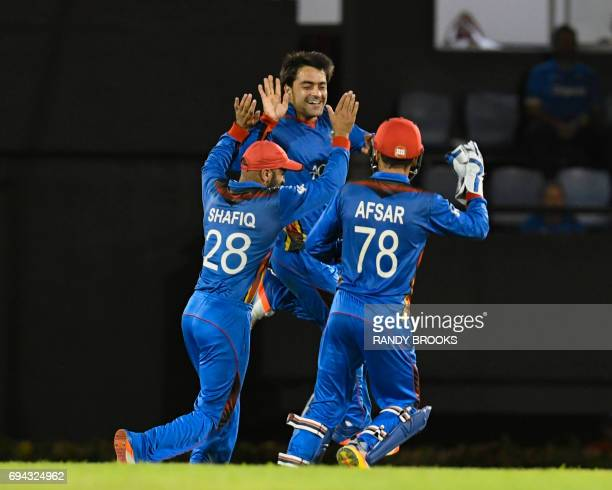 Rashid Khan Shafiqullah Shafaq and Afsar Khan Zazai of Afghanistan celebrate the dismissal of Roston Chase of West Indies during the 1st ODI match...