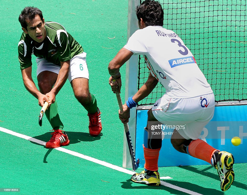 Rashid Mehmood of Pakistan (L) steers the ball past Rupinder Pal Singh of India (R) to score during their men's match on the final day of the International Super Series hockey tournament in Perth on November 25, 2012. AFP PHOTO / Tony ASHBY IMAGE
