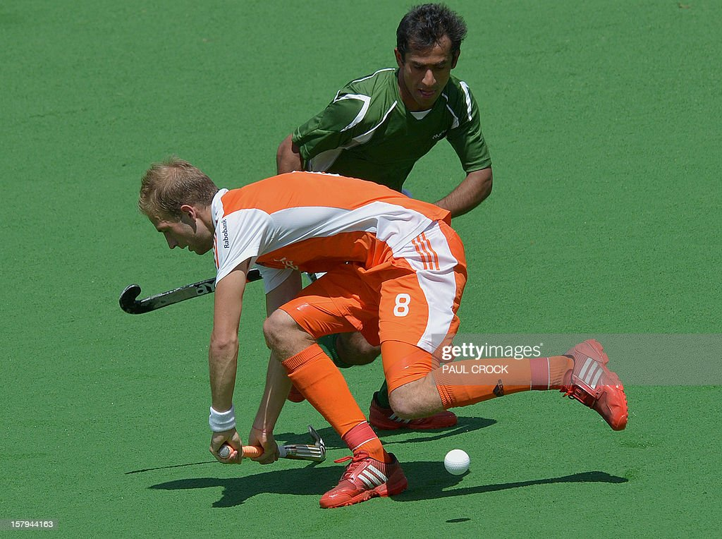 Rasid Mehmood of Pakistan (R) makes a pass through Bill Bakker of The Netherlands (L) during their semi final match at the Men's Hockey Champions Trophy in Melbourne on December 8, 2012. IMAGE STRICTLY RESTRICTED TO EDITORIAL USE - STRICTLY NO COMMERCIAL USE AFP PHOTO/Paul CROCK
