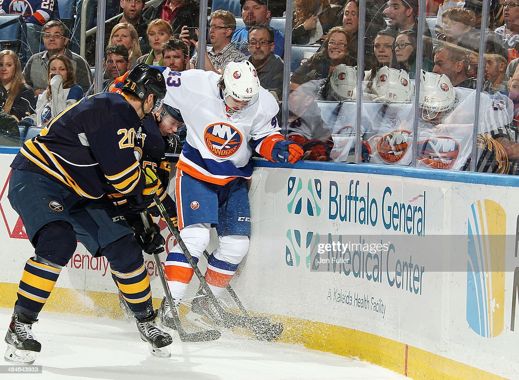 Rasmus Ristolainen #55 and Henrik Tallinder #20 of the Buffalo Sabres battle for the puck along the boards against Mike Halmo #43 of the New York Islanders at First Niagara Center on April 13, 2014 in Buffalo, New York.