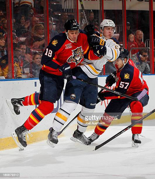 Rasmus Ristolainen of the Buffalo Sabres and Shawn Matthias of the Florida Panthers come together behind the net during first period action at the...