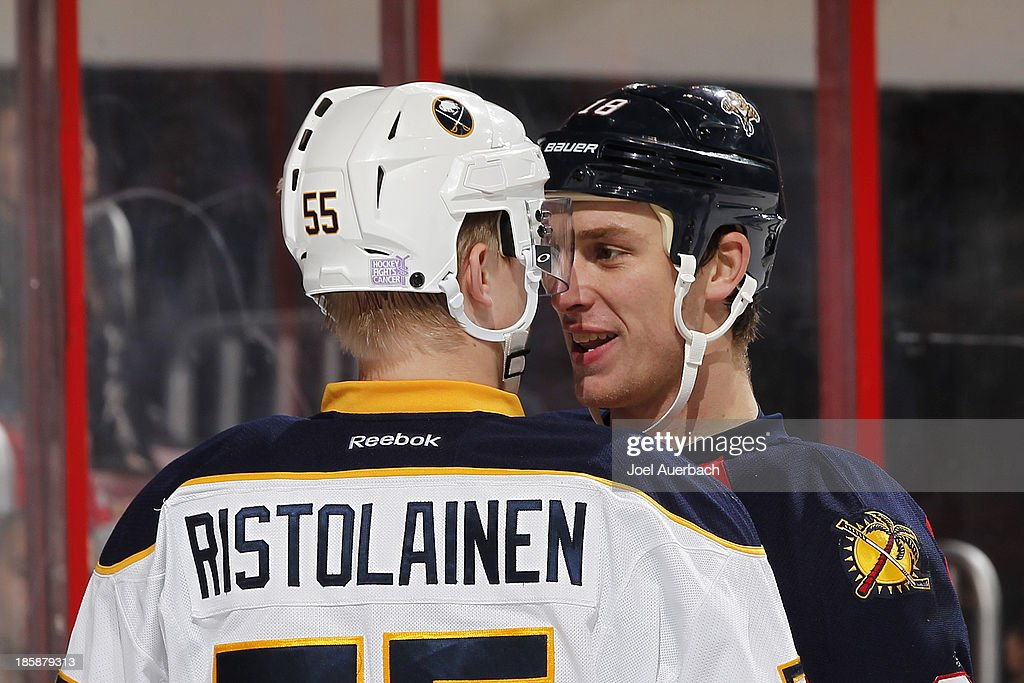 Rasmus Ristolainen #55 of the Buffalo Sabres and Shawn Matthias #18 of the Florida Panthers come together after a hard check behind the net at the BB&T Center on October 25, 2013 in Sunrise, Florida.