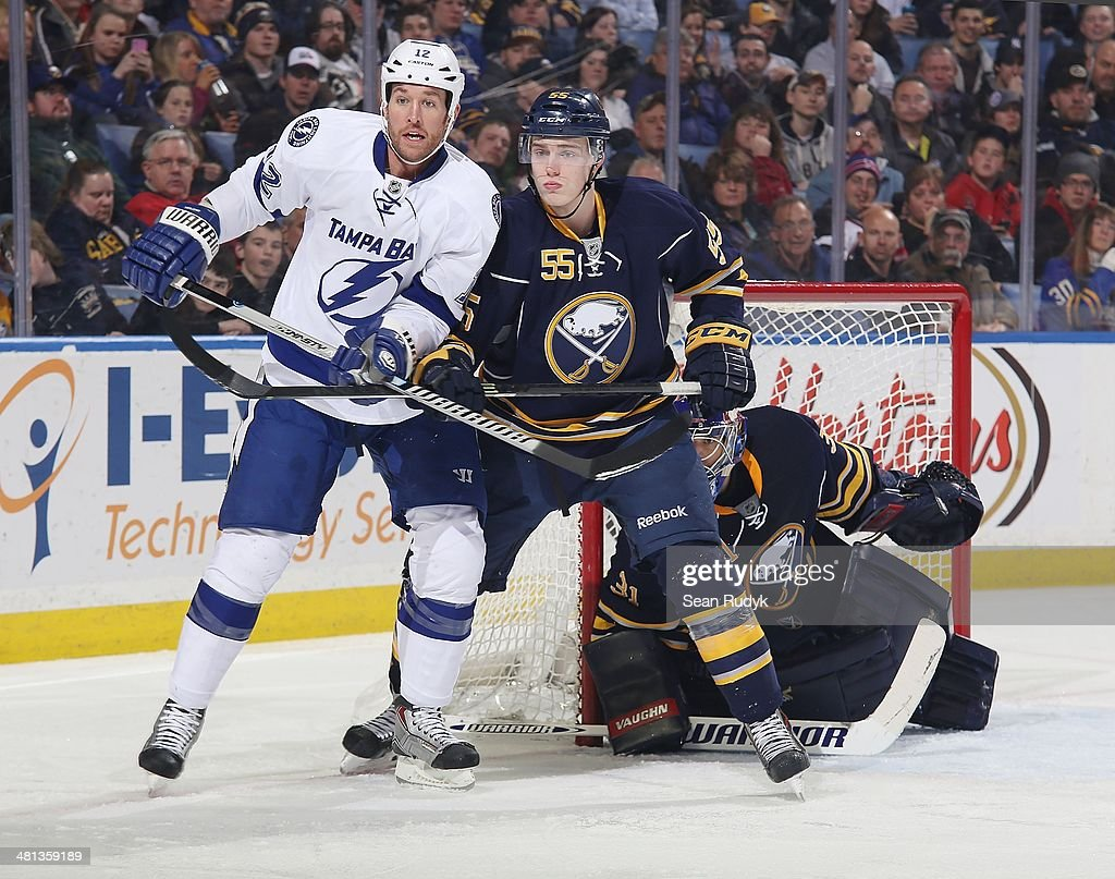 Rasmus Ristolainen of the Buffalo Sabres battles for position with Ryan Malone of the Tampa Bay Lightning in front of Sabres goaltender Matt Hackett...