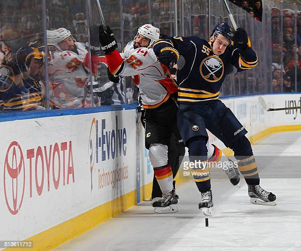 Rasmus Ristolainen of the Buffalo Sabres checks Brandon Bollig of the Calgary Flames into the boards during an NHL game on March 3 2016 at the First...