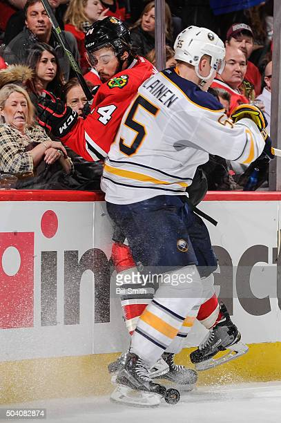 Rasmus Ristolainen of the Buffalo Sabres checks into Phillip Danault of the Chicago Blackhawks in the second period of the NHL game at the United...