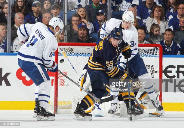Rasmus Ristolainen of the Buffalo Sabres defends against Zach Hyman and Auston Matthews of the Toronto Maple Leafs during an NHL game at the KeyBank...