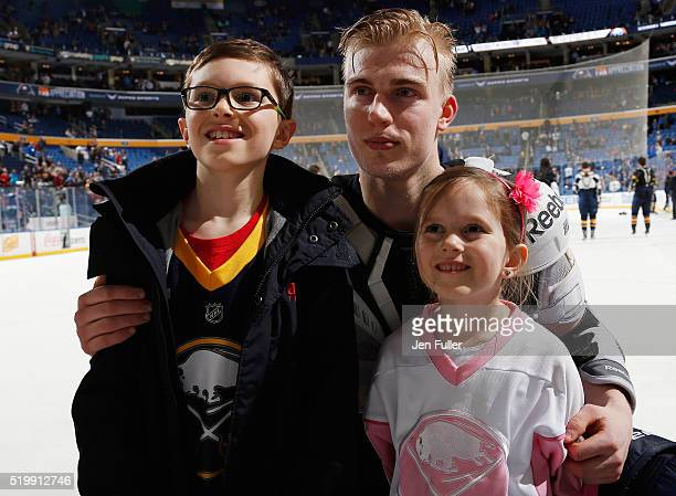 Rasmus Ristolainen of the Buffalo Sabres poses for a photo with young fans during the Jersey Off My Back portion of Fan Appreciation Night following...