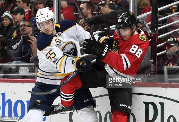 Rasmus Ristolainen of the Buffalo Sabres pushes Patrick Kane of the Chicago Blackhawks in the first period at the United Center on December 8 2017 in...