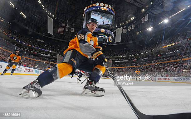 Rasmus Ristolainen of the Buffalo Sabres reaches for the puck along the boards while playing in his 100th NHL career game against the Washington...
