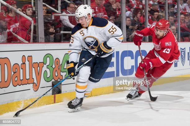 Rasmus Ristolainen of the Buffalo Sabres skates with the puck along the boards followed by Riley Sheahan of the Detroit Red Wings during an NHL game...