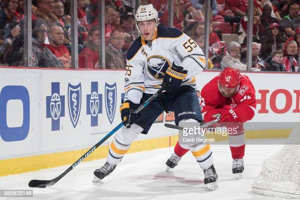 Rasmus Ristolainen of the Buffalo Sabres skates with the puck behind the net followed by Frans Nielsen of the Detroit Red Wings during an NHL game at...