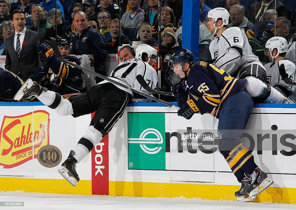 Rasmus Ristolainen #55 of the Buffalo Sabres upends Jordan Nolan #71 of the Los Angeles Kings into between team benches during the second period on November 12, 2013 at the First Niagara Center in Buffalo, New York.