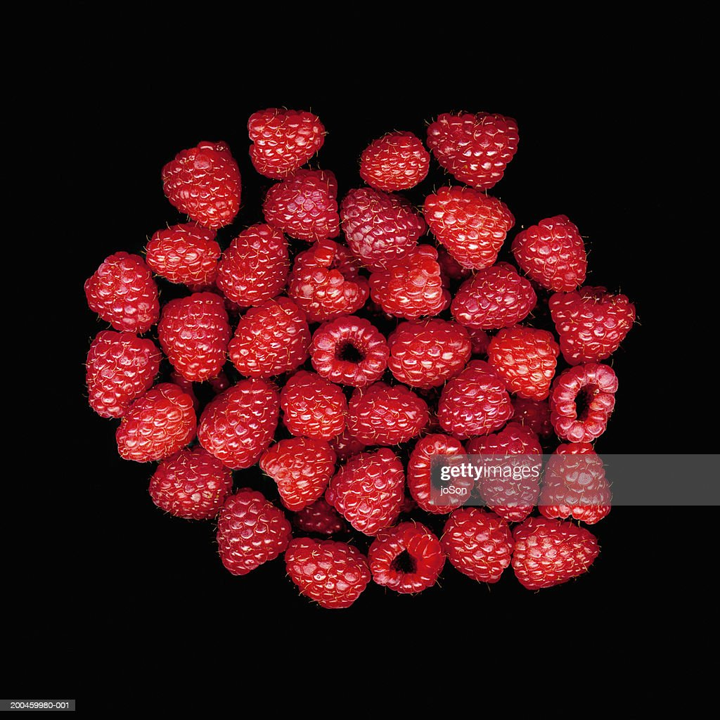 Raspberries against black background, close-up : Stock Photo