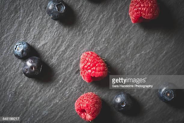Raspberries and blueberries on slate