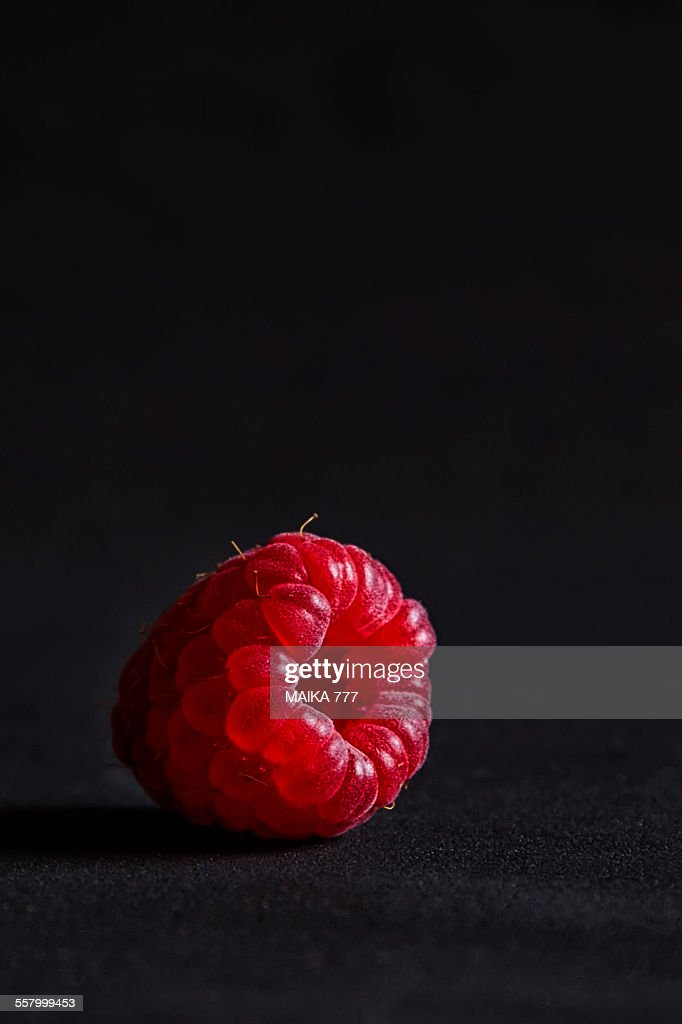 Raspberry against black background, close-up