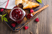 Raspberry jam in a glass jar, fresh croissant and ripe raspberry. Vintage rustic style. Copy space