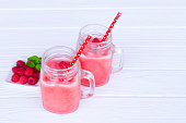 Raspberry smoothies, fruit juices and blueberries on a white wooden background. Drink in the morning for good health.
