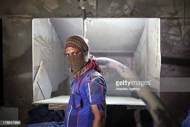 Rassel working for 4 years as an operator of a sand blasting machine in a garment factory is seen on May 22 2013 in Dhaka Bangladesh Bangladeshi...