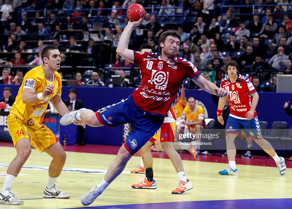 Rastko Stojkovic (C) of Serbia jumps to score past Velko Markoski (L) of Macedonia during the Men's European Handball Championship 2012 second round group one match between Serbia and Macedonia at Arena Hall on January 25, 2012 in Belgrade, Serbia.