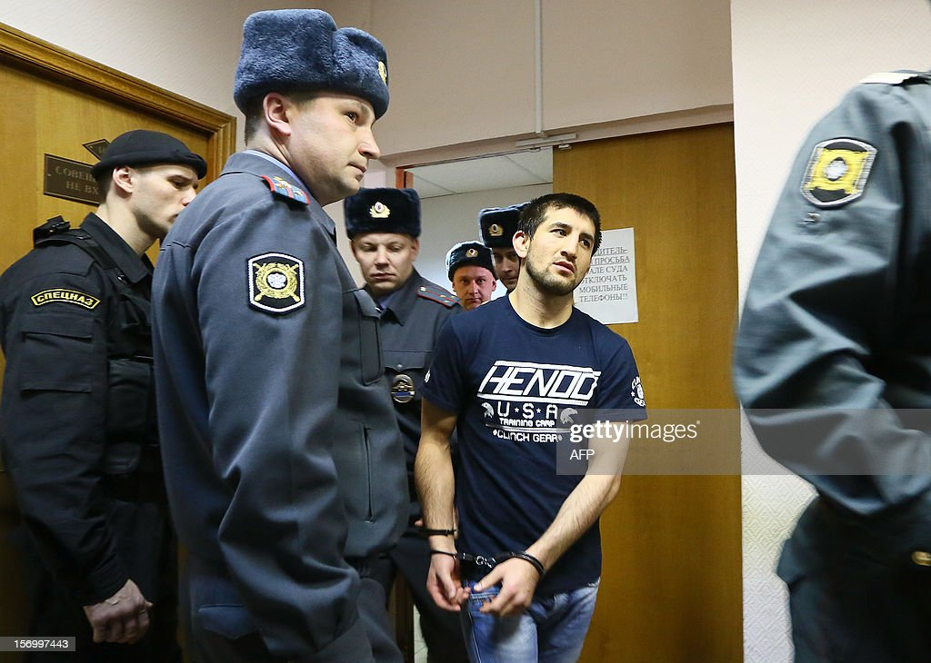 Rasul Mirzayev, a martial arts champion from the North Caucasus who accidentally killed a Russian student in a nightclub brawl (2nd R), is lead handcuffed into a courtroom by police before being sentenced in Moscow, on November 27, 2012.