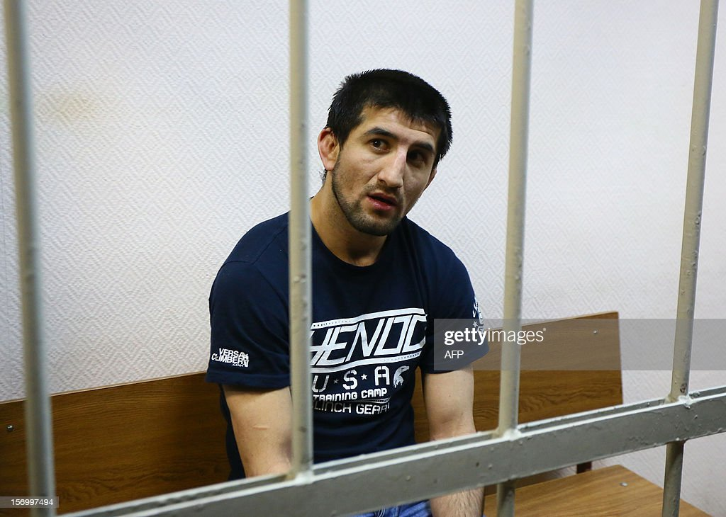 Rasul Mirzayev, a martial arts champion from the North Caucasus who accidentally killed a Russian student in a nightclub brawl (2nd R), sits inside the defendant's cage in a courtroom by police before being sentenced in Moscow, on November 27, 2012.