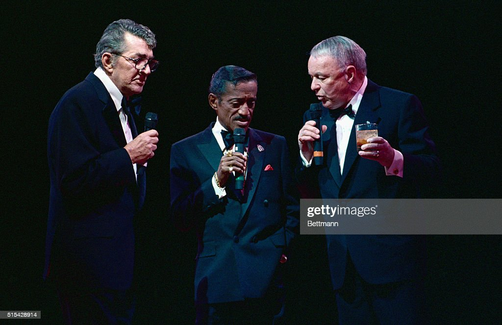 Rat Pack members (L-R) Dean Martin, Sammy Davis, Jr., and Frank Sinatra sing together on stage during a concert tour.