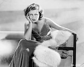 A rather bored looking Joan Crawford wearing a full length evening dress and sitting on her fur trimmed coat