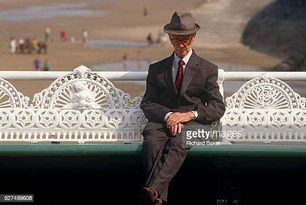 A rather eccentriclooking man is seated on a bench on Blackpool's North Pier This northern seaside resort in the northwest of England is diverse in...