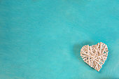 Rattan Woven White Decorative Heart on Turquoise Background Corner Position. Valentine Mother's Day Romantic Greeting Card Banner Poster. Kids Charity Concept Copy Space