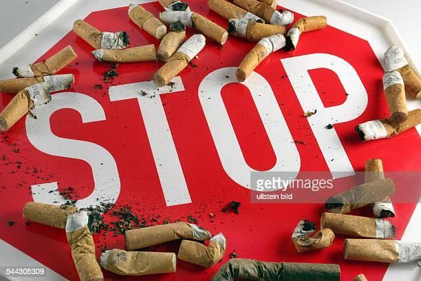 Raucherentwöhnung Rauchen abgewöhnen Rauchverbot rauchfrei Zigarettenkippen auf einem StoppSchild