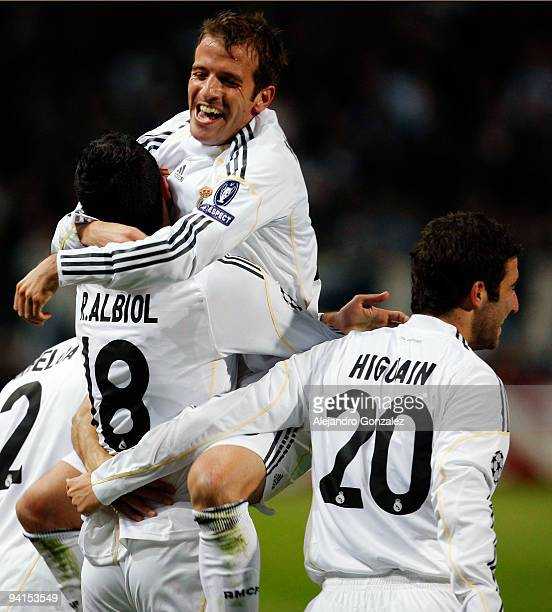 Raul Albiol of Real Madrid celebrates his goal with Rafael Van der Vaart and Gonzalo Higuain during the UEFA Champions League Group C match between...