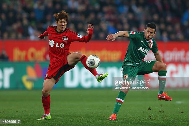Raul Bobadilla of Augsburg battles for the ball with Heung Min Son of Leverkusen during the Bundesliga match between FC Augsburg and Bayer Leverkusen...