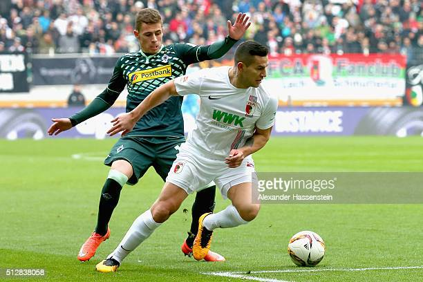 Raul Bobadilla of Augsburg battles for the ball with Thorgan Hazard of Moenchengladbach during the Bundesliga match between FC Augsburg and Borussia...
