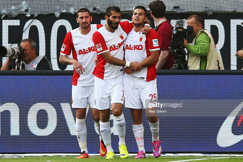 Raul Bobadilla of Augsburg celebrates his team's first goal with team mates Halil Altintop and Sascha Moelders during the Bundesliga match between...