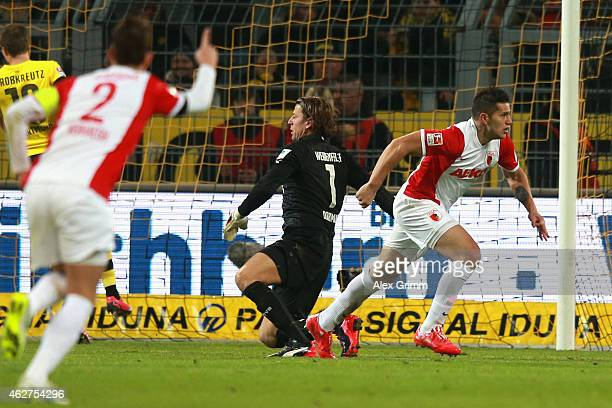 Raul Bobadilla of Augsburg celebrates scoring the opening goal whilst Roman Weidenfeller keeper of Dortmund looks dejected during the Bundesliga...