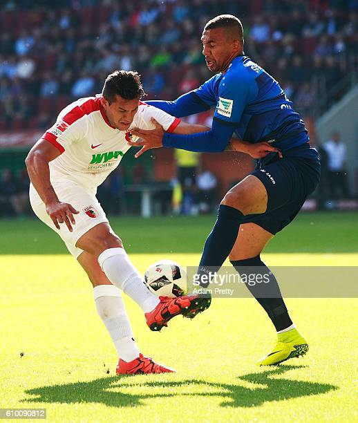 Raul Bobadilla of Augsburg is challenfed by Leon Guwara of SV Darmstadt 98 during the Bundesliga match between FC Augsburg and SV Darmstadt 98 at WWK...