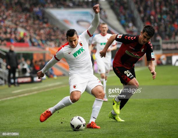 Raul Bobadilla of Augsburg is challenged by MarcOliver Kempf of Freiburg during the Bundesliga match between FC Augsburg and SC Freiburg at WWK Arena...