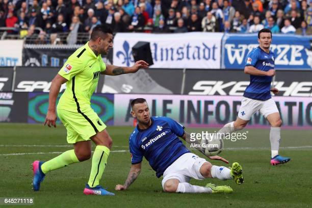 Raul Bobadilla of Augsburg scores his team's second goal past Alexander Milosevic of Darmstadt during the Bundesliga match between SV Darmstadt 98...