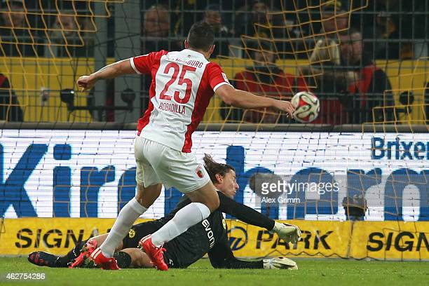 Raul Bobadilla of Augsburg scores the opening goal against Roman Weidenfeller keeper of Dortmund during the Bundesliga match between Borussia...