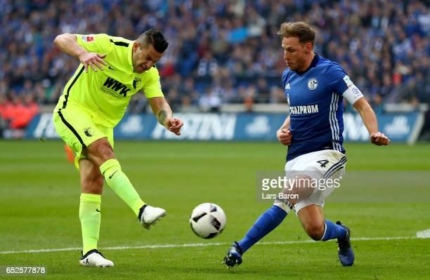 Raul Bobadilla of Augsburg shoots on goal next to Benedikt Hoewedes of Schalke during the Bundesliga match between FC Schalke 04 and FC Augsburg at...