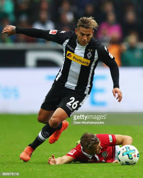 Raul Bobadilla of Borussia Monchengladbach gets past the tackle from Matthias Ostrzolek of Hannover 96 during the Bundesliga match between Borussia...