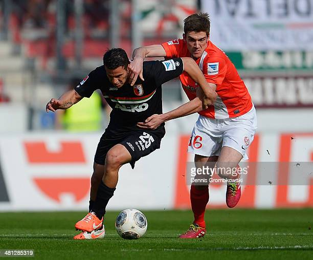 Raul Bobadilla of FC Augsburg and Stefan Bell of Mainz 05 battle for the ball during the Bundesliga match between 1 FSV Mainz 05 and FC Augsburg at...
