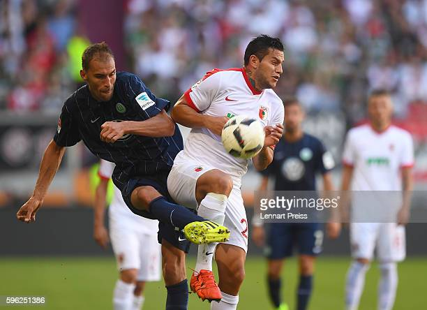 Raul Bobadilla of FC Augsburg challenges Bas Dost of VfL Wolfsburg during the Bundesliga match between FC Augsburg and VfL Wolfsburg at WWK Arena on...