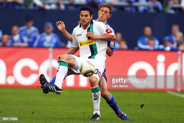 Raul Bobadilla of Moenchengladbach is challenged by Benedikt Hoewedes of Schalke during the Bundesliga match between FC Schalke 04 and Borussia...