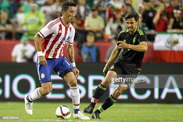 Raul Bobadilla of Paraguay drives the ball followed by Oswaldo Alanis of Mexico during an international friendly match between Paraguay and Mexico at...