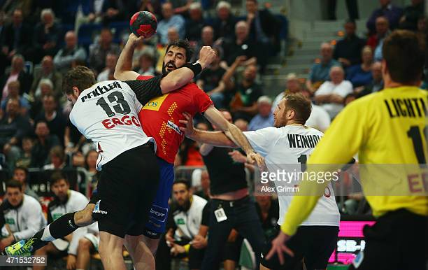 Raul Entrerrios Rodriguez of Spain is challenged by Hendrik Pekeler and Steffen Weinhold of Germany during the European Handball Championship 2016...
