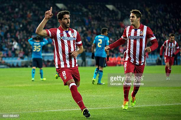 Raul Garcia celebrates scoring their opening goal with teammate Koke during the UEFA Champions League Group G match at Vicente Calderon Stadium on...