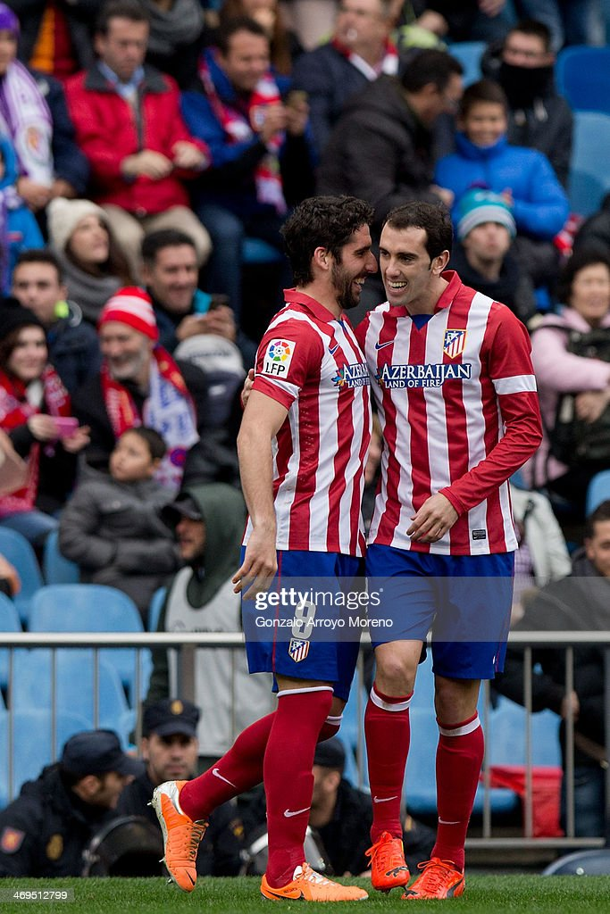 Raul Garcia (L) of Atletico de Madrid celebrates scoring their opening goal with his teammate <a gi-track='captionPersonalityLinkClicked' href=/galleries/search?phrase=Diego+Godin&family=editorial&specificpeople=608999 ng-click='$event.stopPropagation()'>Diego Godin</a> (R) during the La Liga match between Club Atletico de Madrid and Real Valladolid CF at Vicente Calderon Stadium on February 15, 2014 in Madrid, Spain.