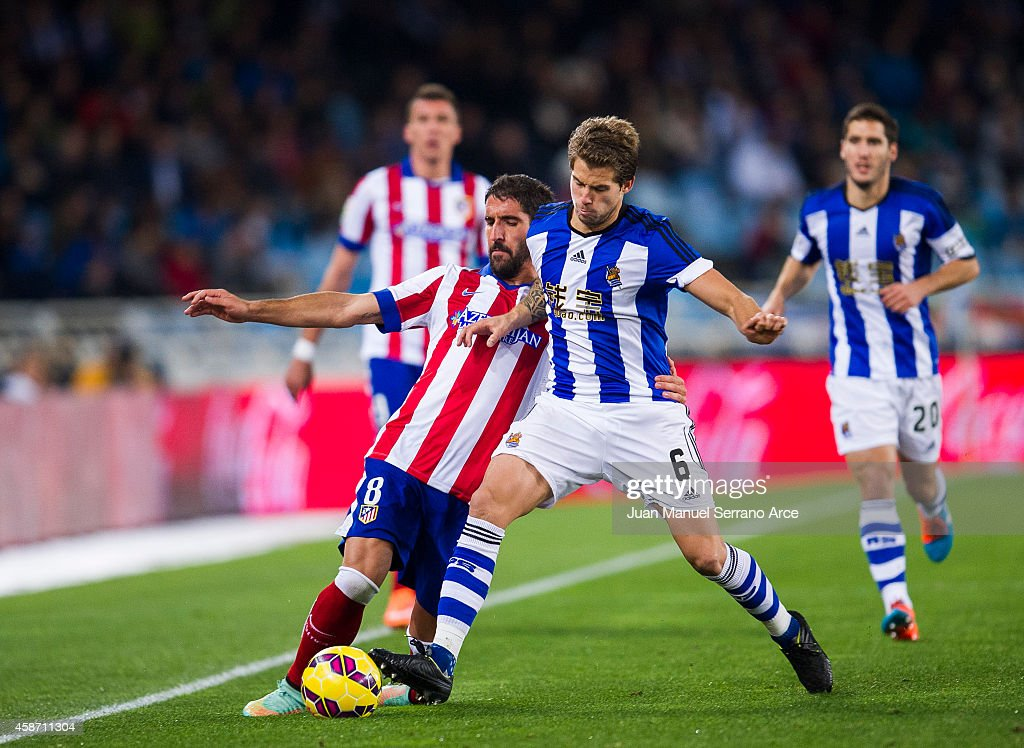 Raul Garcia of Atletico de Madrid duels for the ball with Inigo Martinez of Real Sociedad during the La Liga match between Real Sociedad and Atletico...