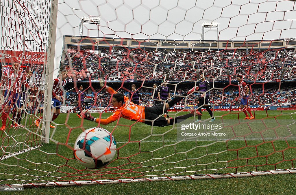 Raul Garcia of Atletico de Madrid scores their opening goal through goalkeeper Diego Marino of Real Valladolid CF during the La Liga match between Club Atletico de Madrid and Real Valladolid CF at Vicente Calderon Stadium on February 15, 2014 in Madrid, Spain.